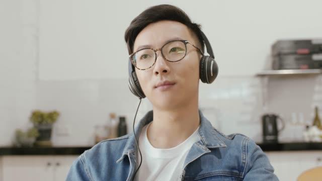 男が台所でヘッドフォンで音楽を聴いてください。