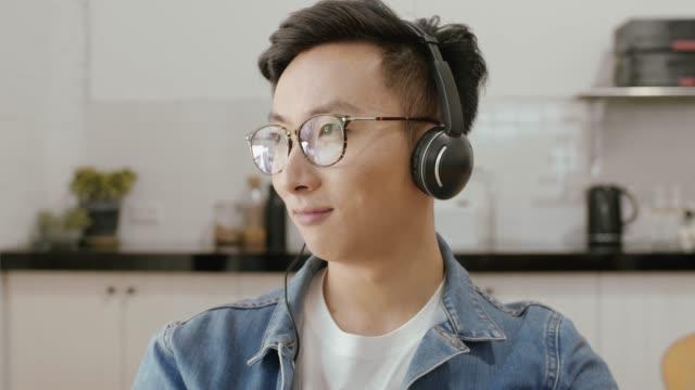 男はキッチン (スローモーション) でヘッドフォンで音楽を聴いてください。