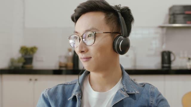台所ではヘッドフォンをポッド キャストに耳を傾ける人