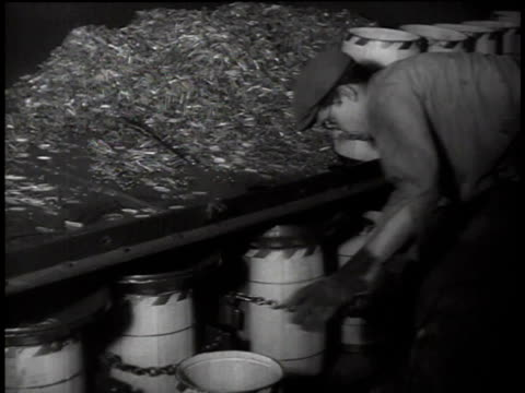 1938 HA Man Loading and unloading shaking barrels, catching steel shavings, beneath a table / Oakland, California, United States