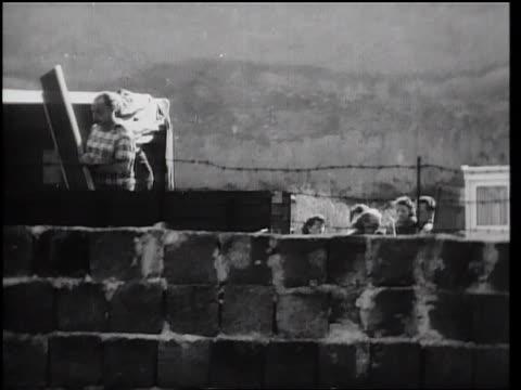 vídeos de stock, filmes e b-roll de pan man loading belongings onto truck behind berlin wall / east berlin germany - muro