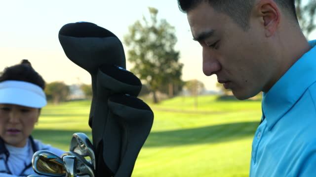 ms ts man loading golf bag onto cart before playing golf with mother and sister - kopfbedeckung stock-videos und b-roll-filmmaterial