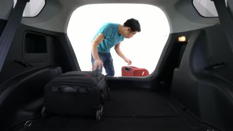 man laddar bagage in bakluckan på bilen - lasta bildbanksvideor och videomaterial från bakom kulisserna