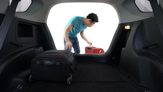 man loading luggage into boot of car - loading stock videos & royalty-free footage