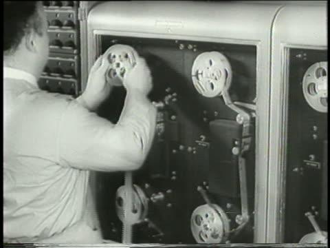 b/w 1958 rear view man loading reel on computer - 1950 video stock e b–roll