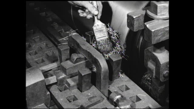 man loading spools of cable onto hand truck inside storage room; coils of wire sliding onto the conveyor belt inside factory; man standing in front... - 1940 1949 video stock e b–roll