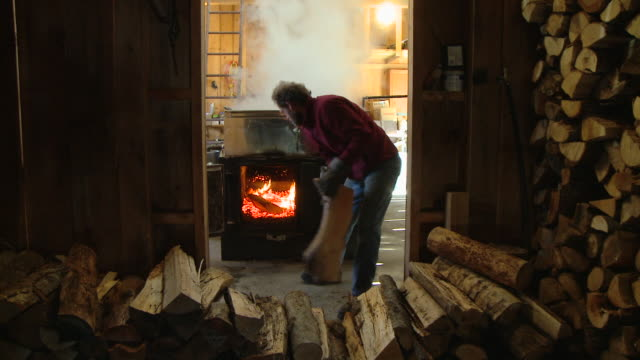 ws man loading wood to fire under boiler with sap in sugar cabin, north conway, new hampshire, usa - boiler stock videos & royalty-free footage