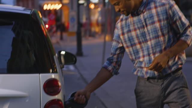 man locking car charging at ev station - checked pattern stock videos & royalty-free footage
