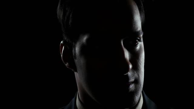 vídeos de stock e filmes b-roll de man looking around in complete darkness at night time - olhar em redor