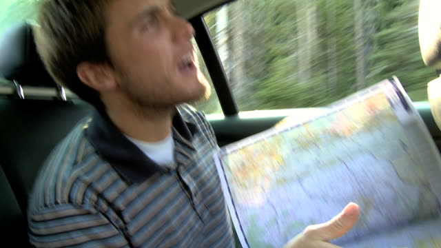 man looking at a map in the back seat of a car on a road trip - lost stock videos & royalty-free footage