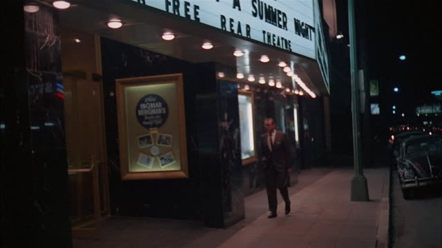 pan man looking at announcement on movie marquis at night, los angeles - film industry stock videos & royalty-free footage