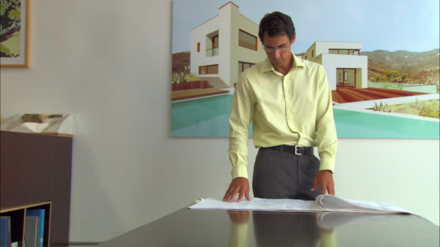 ms, man looking at architectural blueprint at desk, house poster in background - poster layout stock videos & royalty-free footage