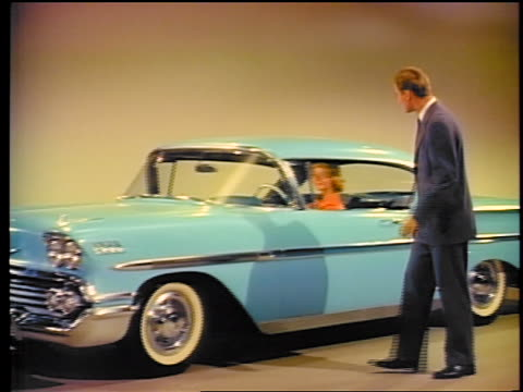 1958 pan man looking at blue chevy impala with woman in it in showroom / commercial - 1958 stock-videos und b-roll-filmmaterial