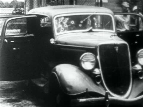 stockvideo's en b-roll-footage met man looking at bonnie and clyde's car full of bullet holes / louisiana - 1934