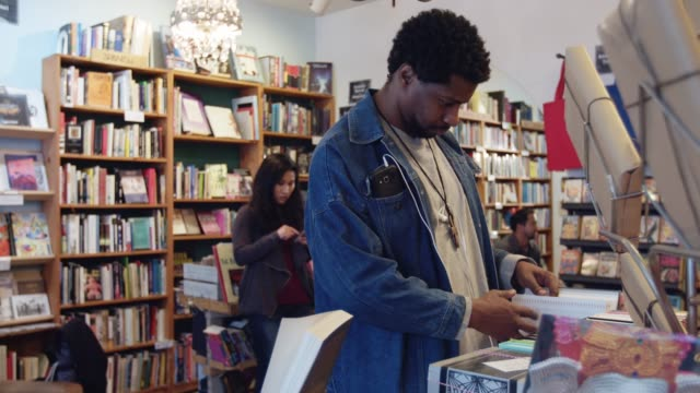 man looking at book in store - book shop stock videos & royalty-free footage