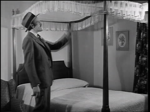 vidéos et rushes de b/w 1935 man looking at canopy + sitting on bed in master bedroom of model home / educational - 1935