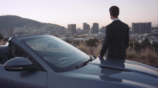 vídeos de stock e filmes b-roll de homem olhando na cidade - convertible