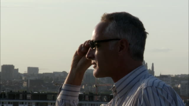cu man looking at cityscape then leaving, brussels, belgium - 横顔点の映像素材/bロール