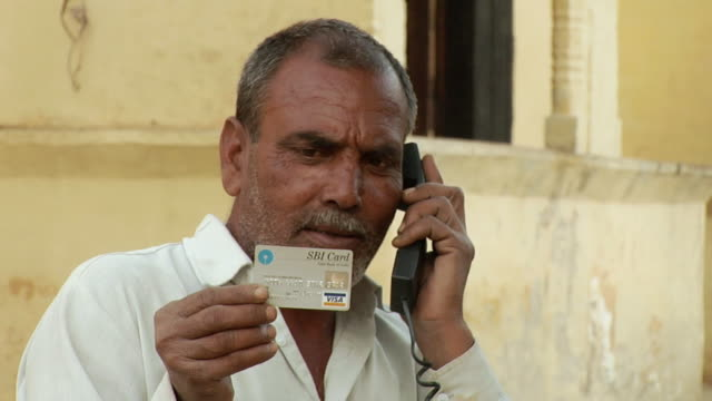 cu man looking at credit card and talking on landline phone / hasanpur, mewat, haryana, india - 受話器点の映像素材/bロール