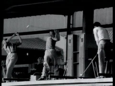 vídeos de stock, filmes e b-roll de man looking at golf club in department store / men practicing golf shots at threetiered golf range / nets of golf balls as woman picks one up and... - 1964