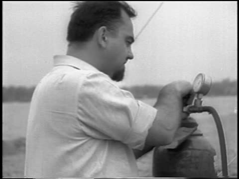 B/W 1933 man looking at guage of gas cannister / first liquidfueled rocket launch / newsreel