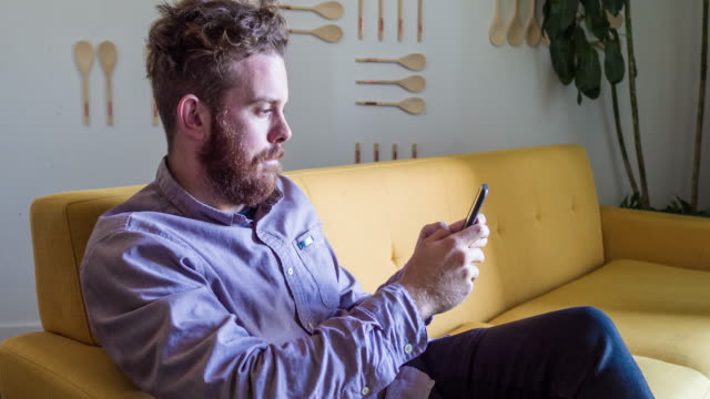 Man looking at his cellphone relaxed at home
