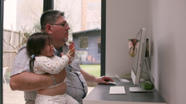 a man looking at his computer at home while he holds his young daughter - candid stock videos & royalty-free footage