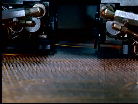 1970 CU Man looking at machinery/ CU Machine threading yellow wire / CU Needle on machine