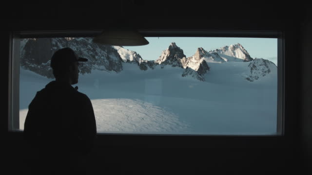 Man looking at mountain peaks through hut window in Swiss Alps
