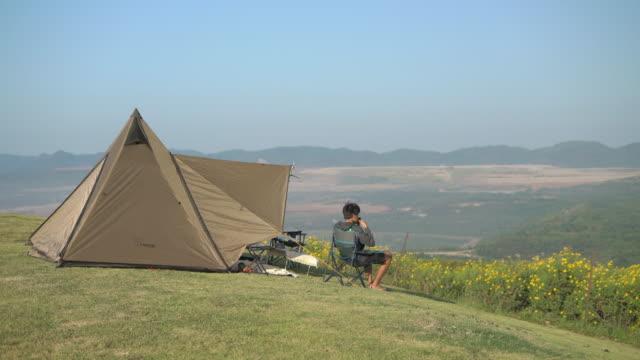コーヒーを飲んでキャンプ旅行で山を見ている男 - キャンプする点の映像素材/bロール