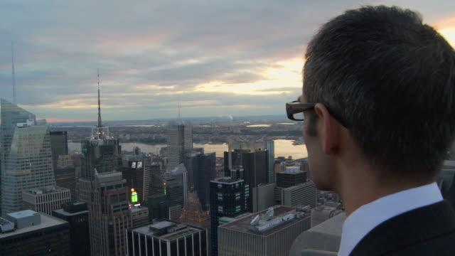 cu man looking at new york cityscape at sunset / new york, usa - 見る点の映像素材/bロール