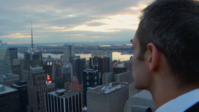 vídeos de stock, filmes e b-roll de cu man looking at new york cityscape at sunset / new york, usa - horizonte