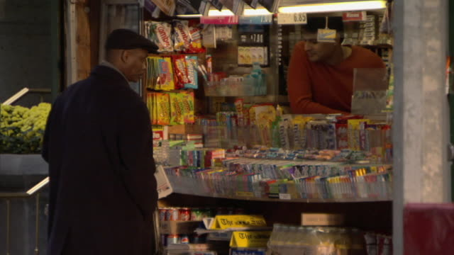 vidéos et rushes de ms man looking at news stand merchandise while pedestrians walk past / manhattan, new york, usa - kiosque à journaux