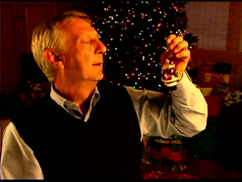 man looking at santa claus christmas ornament - see other clips from this shoot 1407 stock videos and b-roll footage
