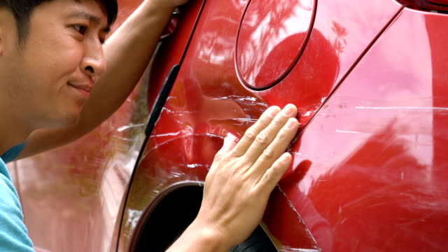 Man Looking At Scratches On His Car.