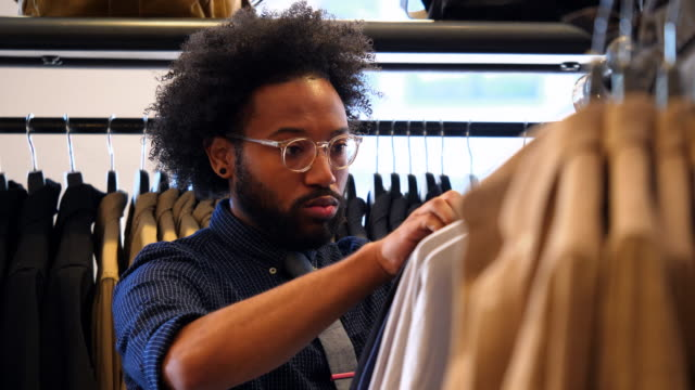 MS Man looking at shirts while shopping in mens clothing boutique