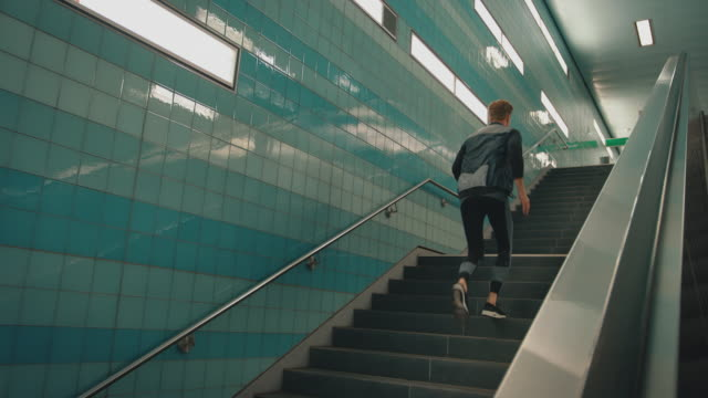 vídeos de stock e filmes b-roll de man looking at smart watch while jogging on steps - degraus