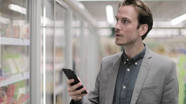 man looking at smartphone in a grocery store - label stock videos & royalty-free footage