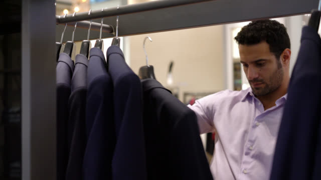 man looking at suits on a rack and trying a jacket on - fare spese video stock e b–roll