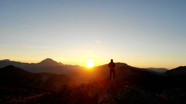 man looking at sunrise in the top of a mountain, aerial - horizont über land stock-videos und b-roll-filmmaterial