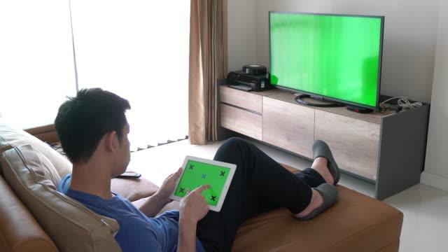 Homme regardant la télévision avec écran vert