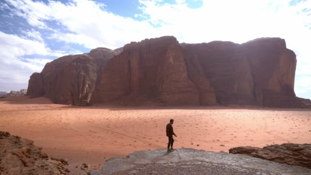 man looking at  wadi rum desert from rock - rock formation stock videos & royalty-free footage
