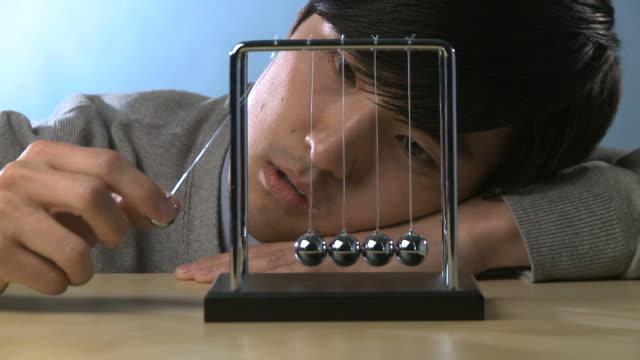 stockvideo's en b-roll-footage met man looking bored playing with kinetic balls - slinger van newton