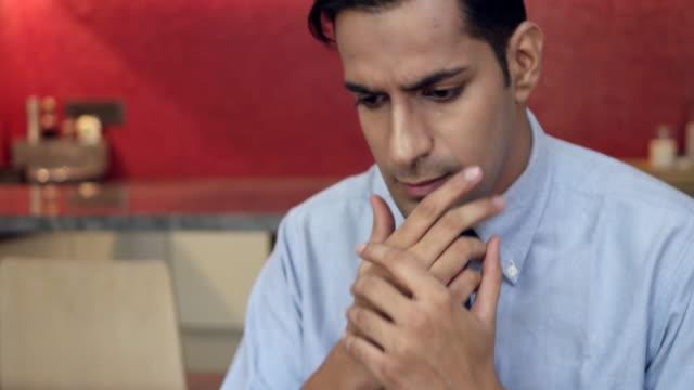 man looking concerned working on his tablet at home and calls someone up from his mobile phone to solve problem - skjorta och slips bildbanksvideor och videomaterial från bakom kulisserna
