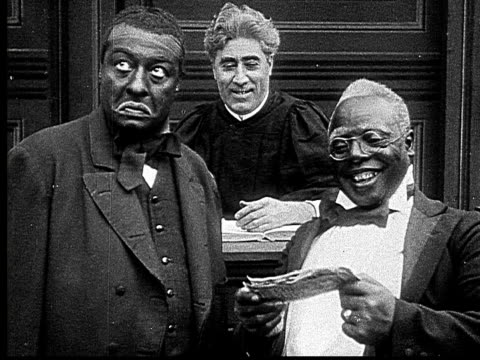 stockvideo's en b-roll-footage met 1916 b&w ms man looking disapprovingly as judge gives other man money/ man leaving with money/ defendant attempting to leave courtroom before being called back by judge  - racisme