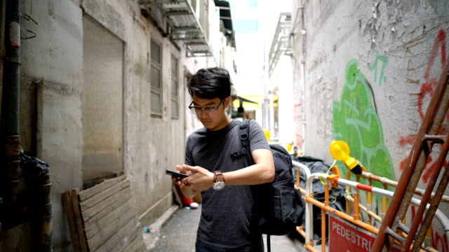 man looking for direction on smartphone in hong kong city - tripping falling stock videos and b-roll footage