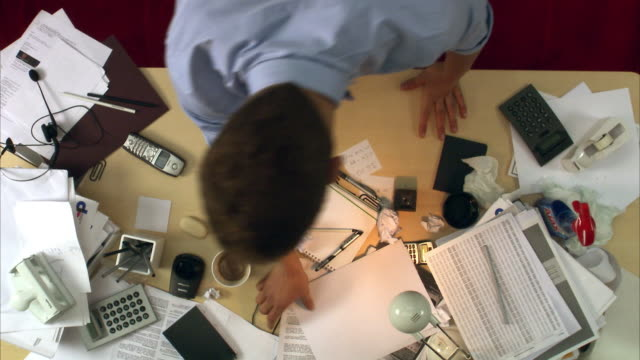 a man looking for keys on a messy desk sweden. - chaos stock-videos und b-roll-filmmaterial