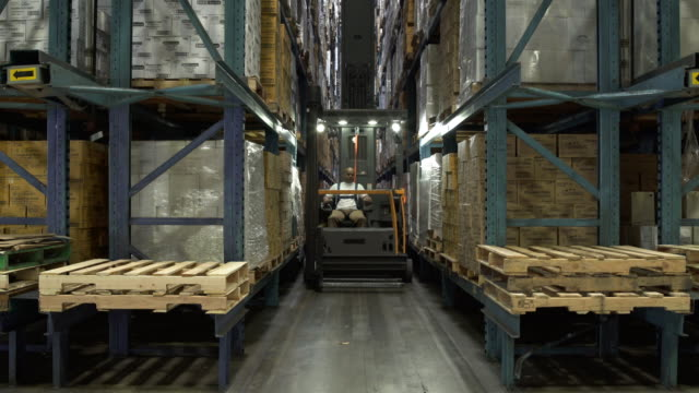 Man looking forward and reversing machinery in warehouse aisle