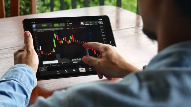 stockvideo's en b-roll-footage met man op zoek grafiek of stock in digitale tablet - graph