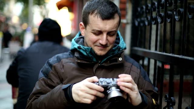 man looking his digital camera - digital camera stock videos and b-roll footage